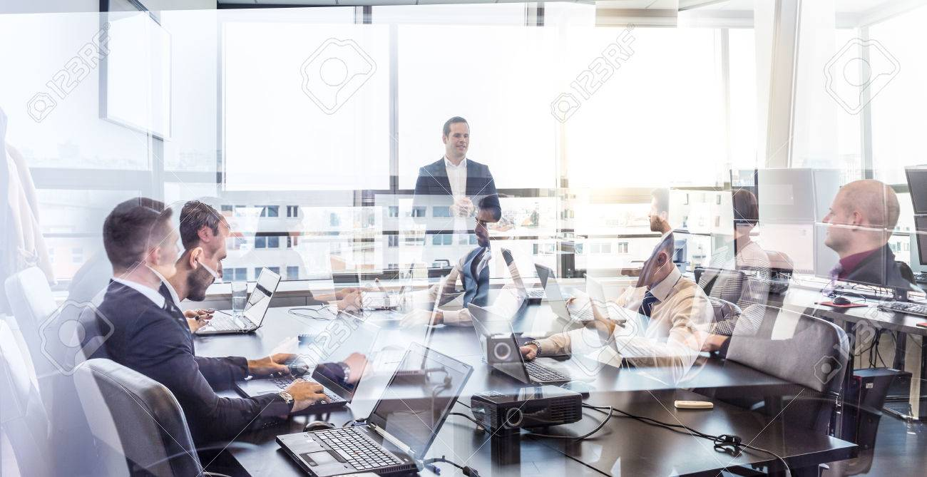 Successful team leader and business owner leading informal in-house business meeting. Business people working on laptops in foreground and glass reflections. Business and entrepreneurship concept. Standard-Bild - 70576697