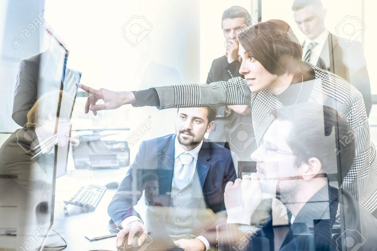Business team looking at data on multiple computer screens in corporate office. Businesswoman pointing on screen. Business people trading online. Business, entrepreneurship and team work concept. Standard-Bild - 72164611