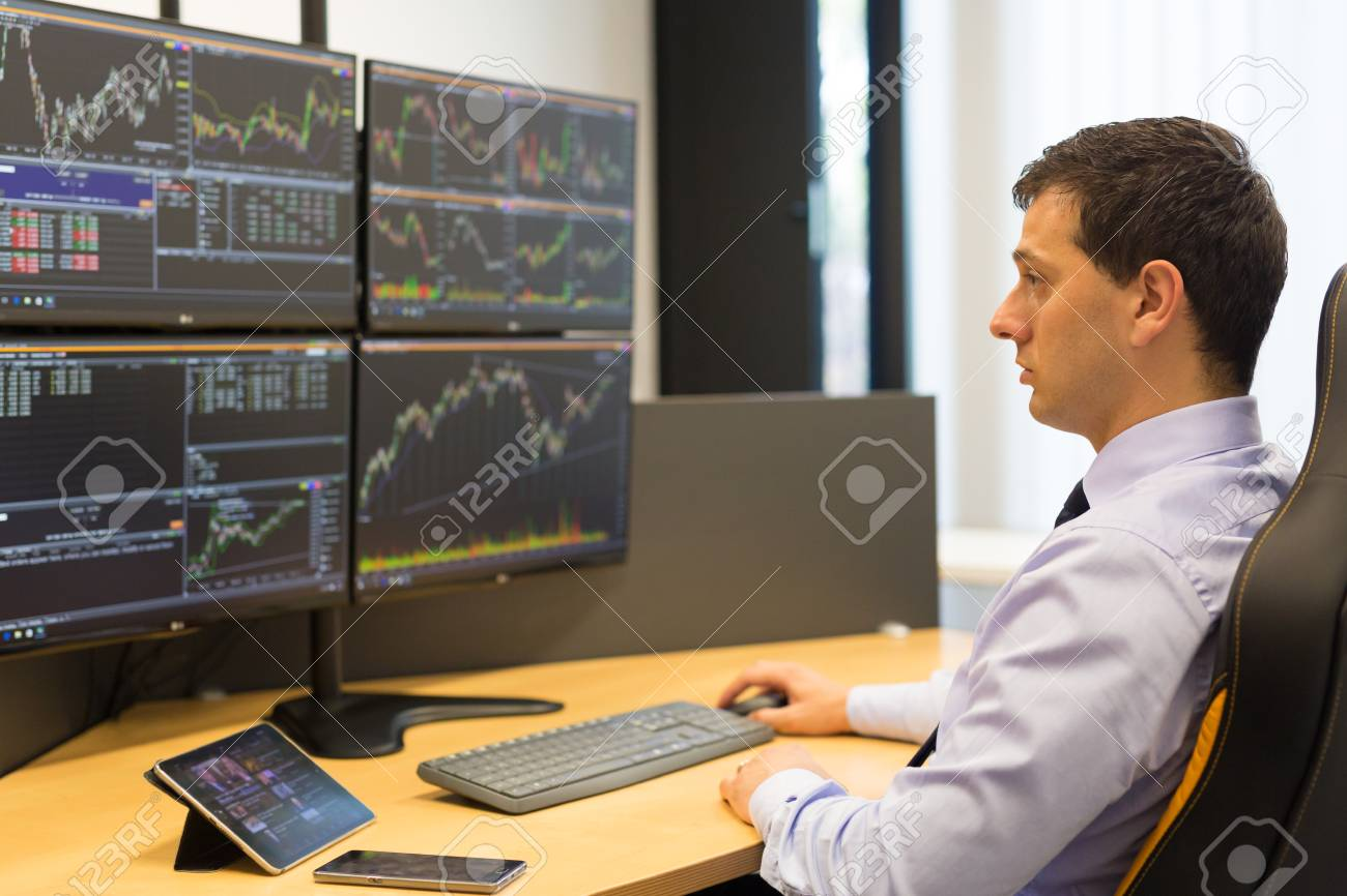 Stock broker trading online while accepting orders by phone stock stock broker trading online while accepting orders by phone traders office with multiple computer screens geenschuldenfo Image collections