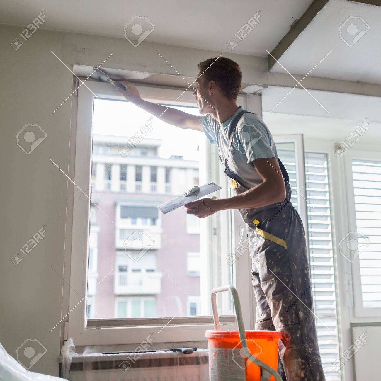Attractive Stock Photo   Thirty Years Old Manual Worker With Wall Plastering Tools  Inside A House. Plasterer Renovating Indoor Walls And Ceilings With Float  And ...