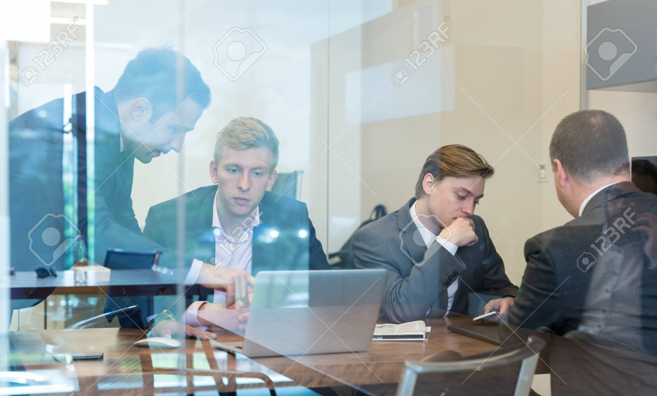 Business People Sitting And Brainstorming At Corporate Meeting