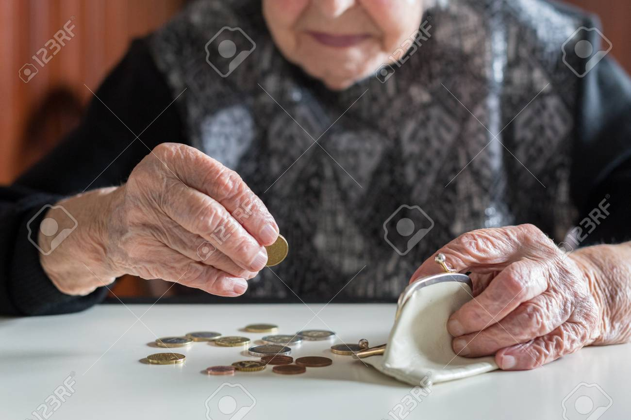 Elderly 95 years old woman sitting miserably at the table at home and counting remaining coins from the pension in her wallet after paying the bills. - 101275167