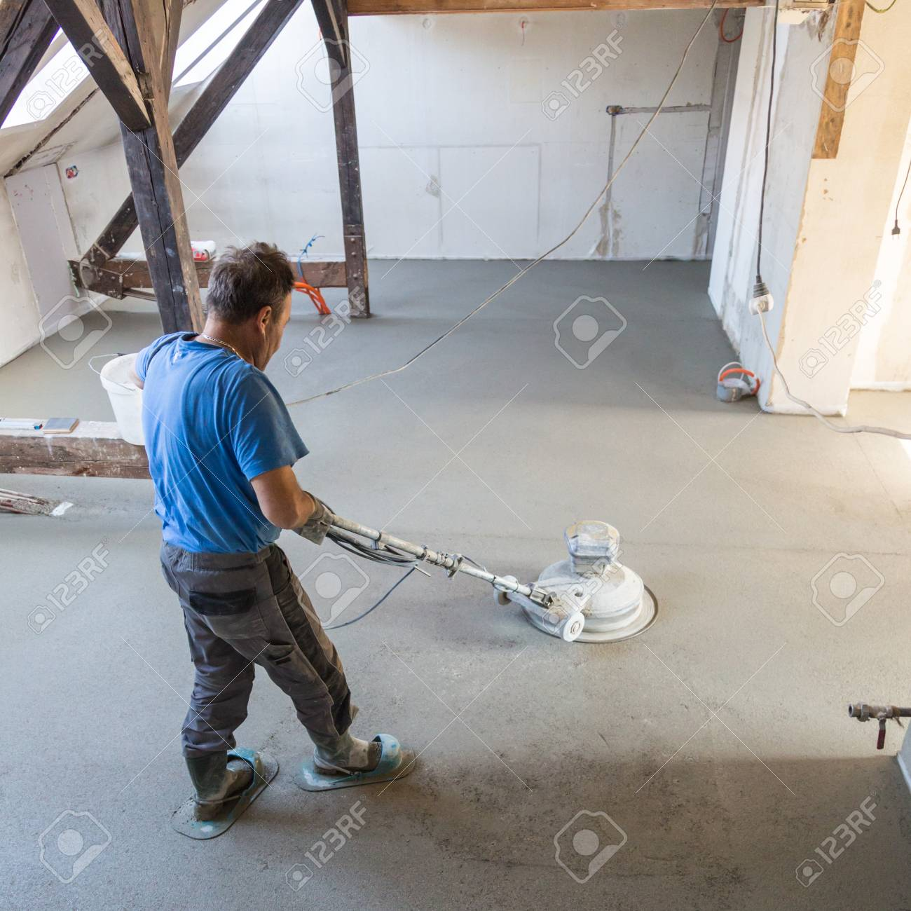 Laborer Performing And Polishing Sand And Cement Screed Floor