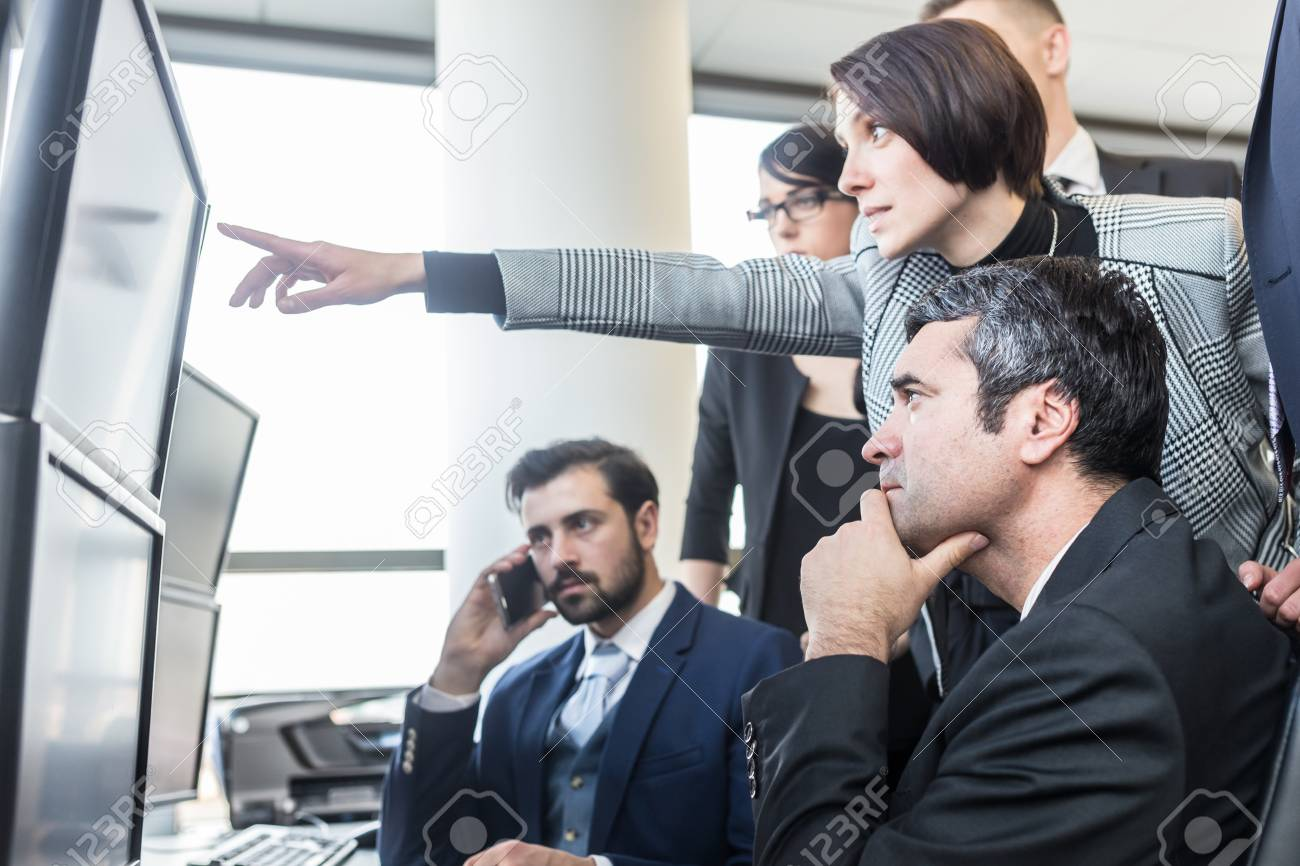 Business people looking at data on multiple computer screens in corporate office. Businesswoman pointing on screen. Business team trading online. Business, entrepreneurship and team work concept. - 122325631