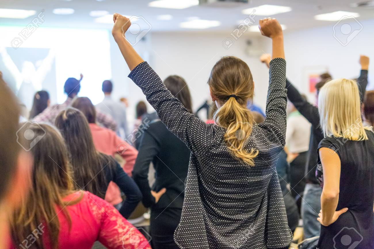 Life coaching symposium. Speaker giving interactive motivational speech at business workshop. Rear view of unrecognizable participants feeling empowered and motivated, hands raised high in air. - 122325833
