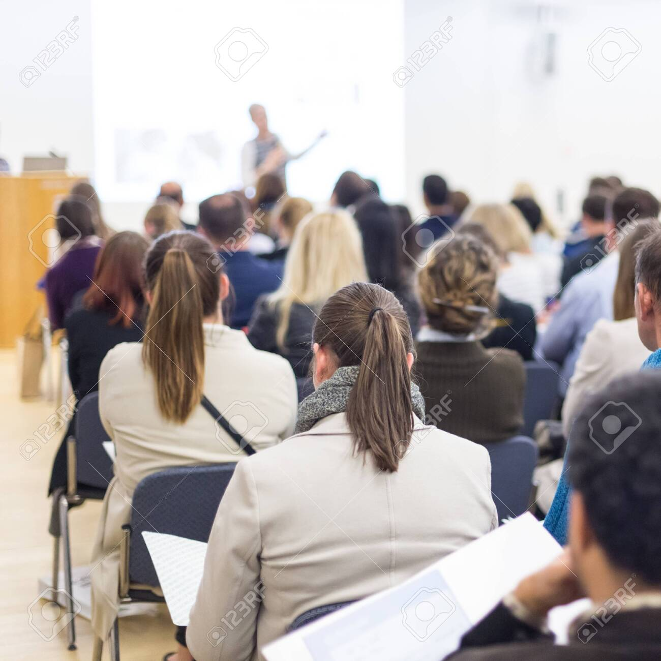 Business and entrepreneurship symposium. Female speaker giving a talk at business meeting. Audience in conference hall. Rear view of unrecognized participant in audience. Copy space on whitescreen. - 123558614