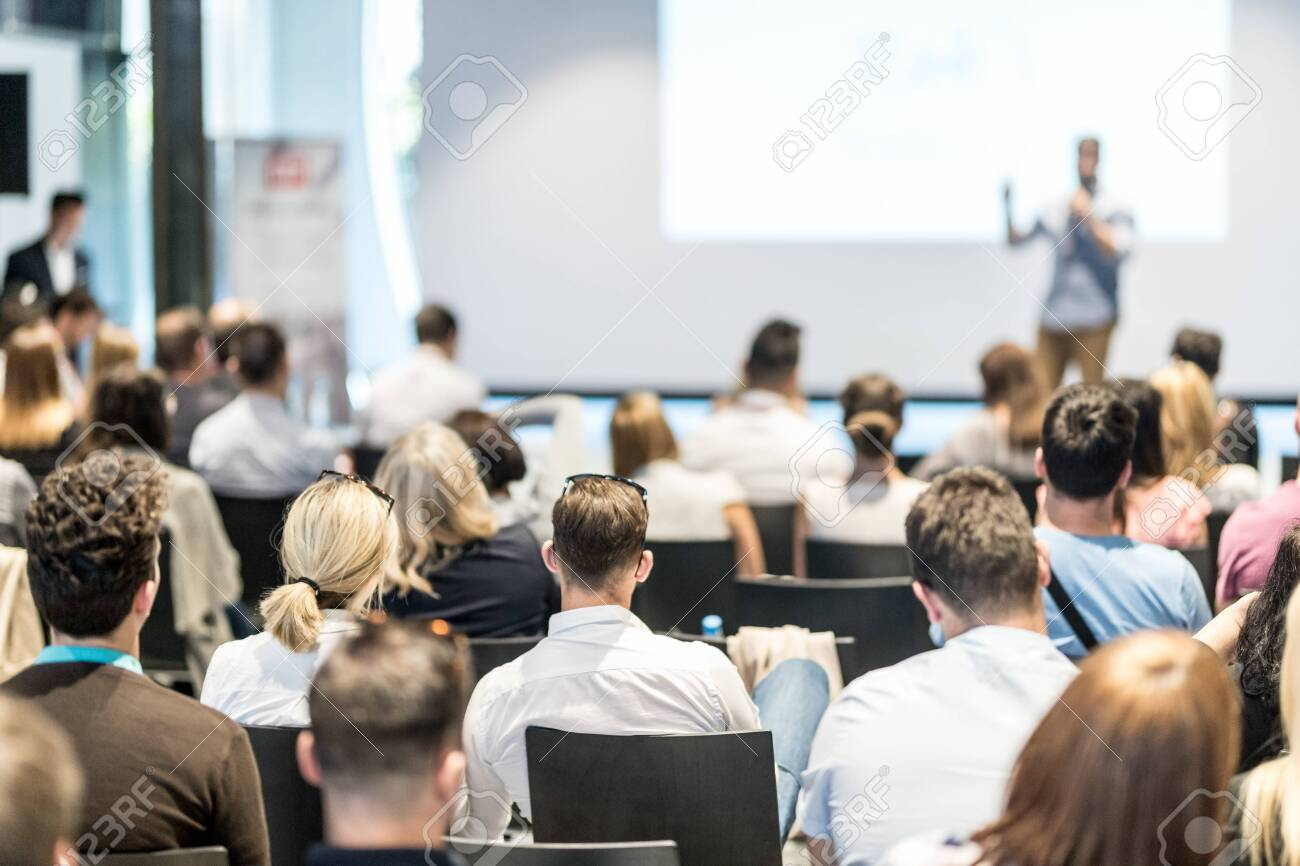 Business and entrepreneurship symposium. Speaker giving a talk at business meeting. Audience in conference hall. Rear view of unrecognized participant in audience. - 128825158
