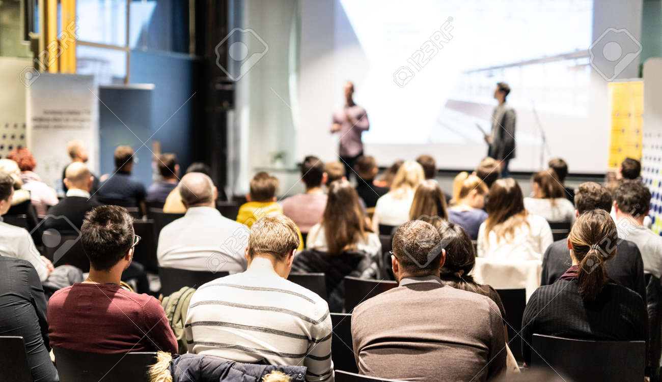 Speaker giving a talk in conference hall at business event. Audience at the conference hall. Business and Entrepreneurship concept. Focus on unrecognizable people in audience. - 138508124