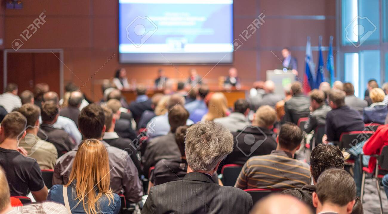 Business and entrepreneurship symposium. Speaker giving a talk at business meeting. Audience in conference hall. Rear view of unrecognized participant in audience. - 141964617