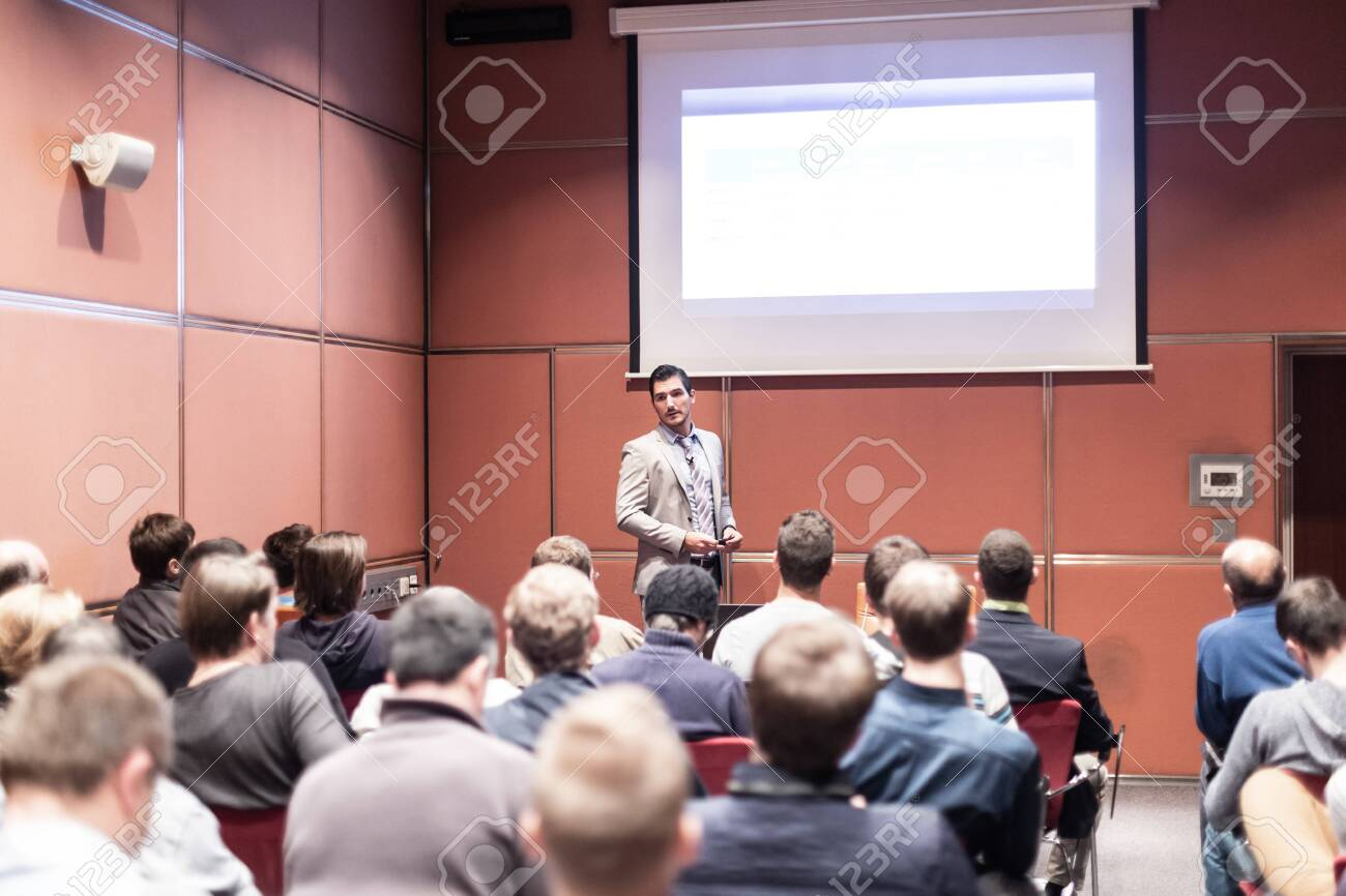 Speaker giving a talk in conference hall at business meeting event. Rear view of unrecognizable people in audience at the conference hall. Business and entrepreneurship concept. - 146714432