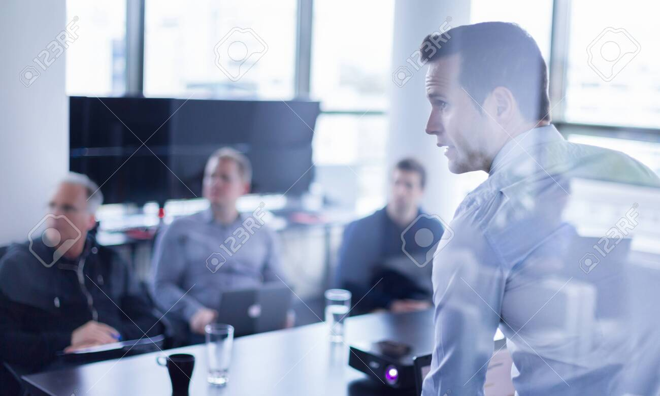 Businessman making a presentation at office. Business executive delivering a presentation to his colleagues during meeting or in-house business training, explaining business plans to his employees. - 147322561