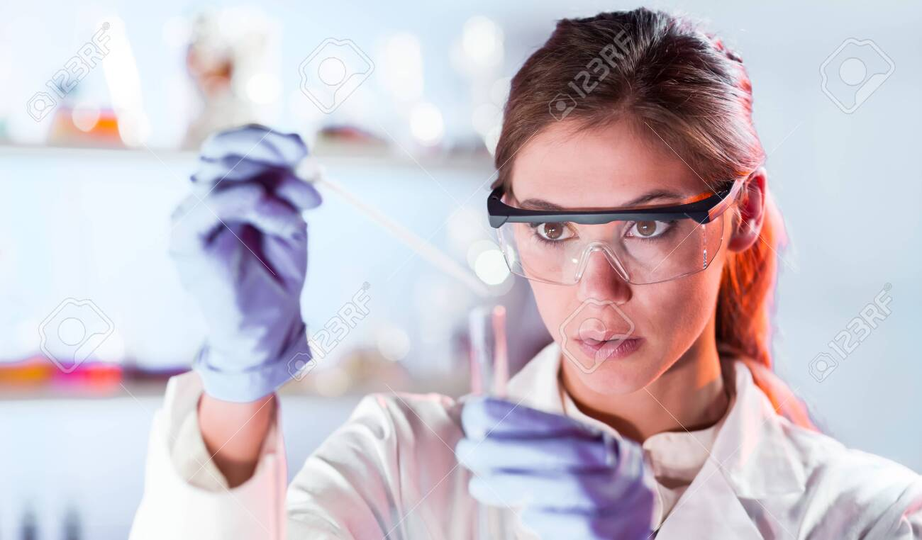 Life scientists researching in laboratory. Focused female life science professional pipetting solution into the glass cuvette. Lens focus on researchers eyes. Healthcare and biotechnology concept. - 154280475