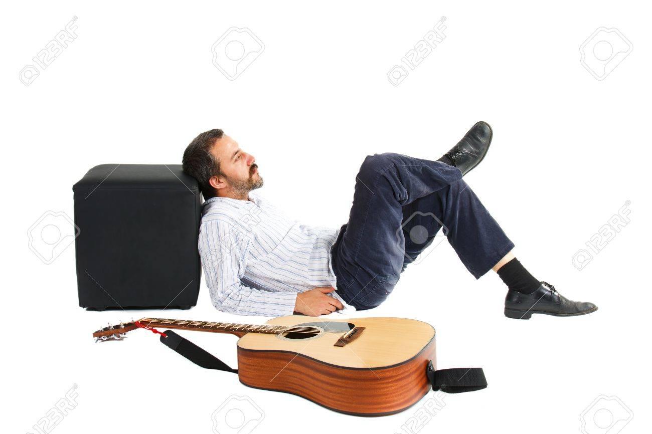 Un giovane con baffi e barba è sdraiato sul pavimento con gli occhi