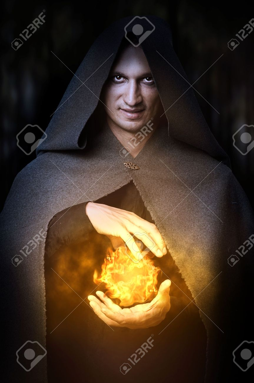 Halloween concept. Powerful Male witch or wizard with fireball in hands. Ball from fire burns Stock Photo - 10465922