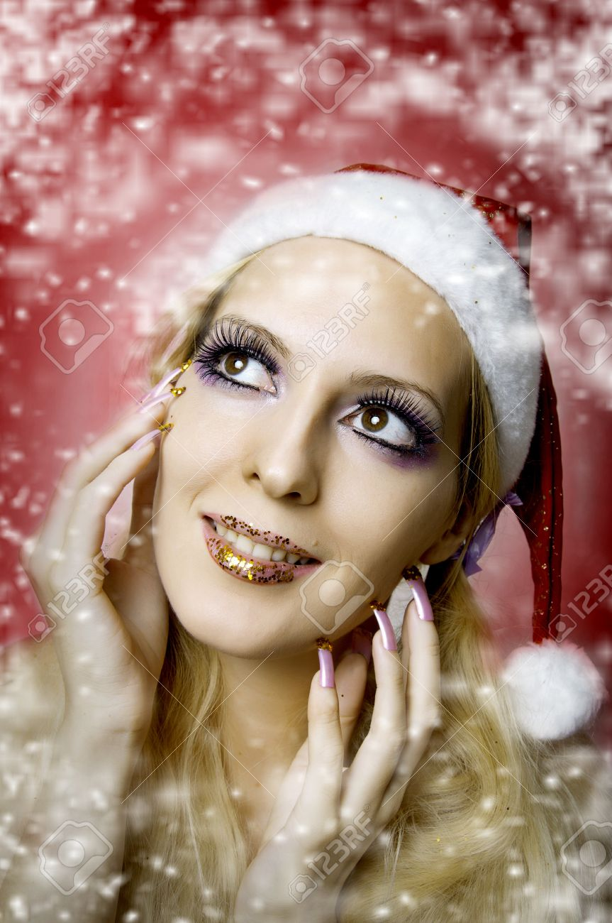 Christmas bright make-up and long nails manicure concept. Portrait of young woman model at santa hat, face closeup Stock Photo - 10522332