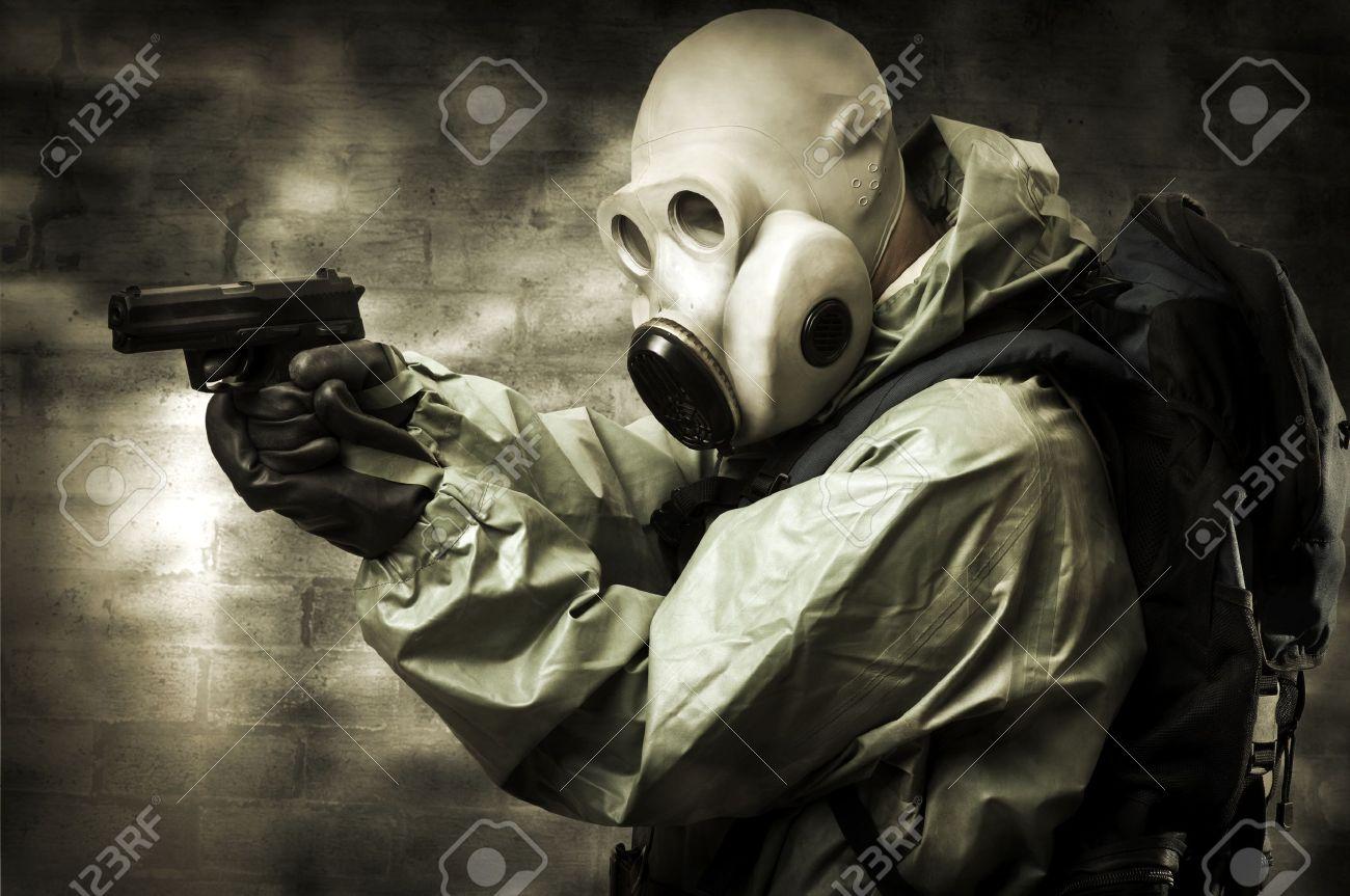 Post apocalypses world halloween concept. Portrair of man in gas mask with handgun Stock Photo - 10623765