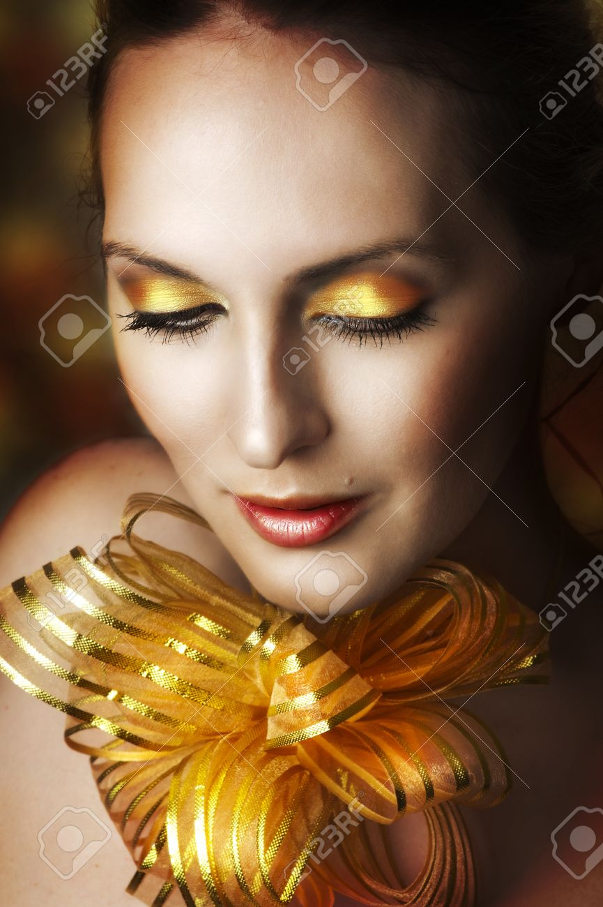 Glamour portrait of young fashion woman face with bright evening golden make up for party and gold ribbon on neck. Concept - make-up as christmas gift - 11242618
