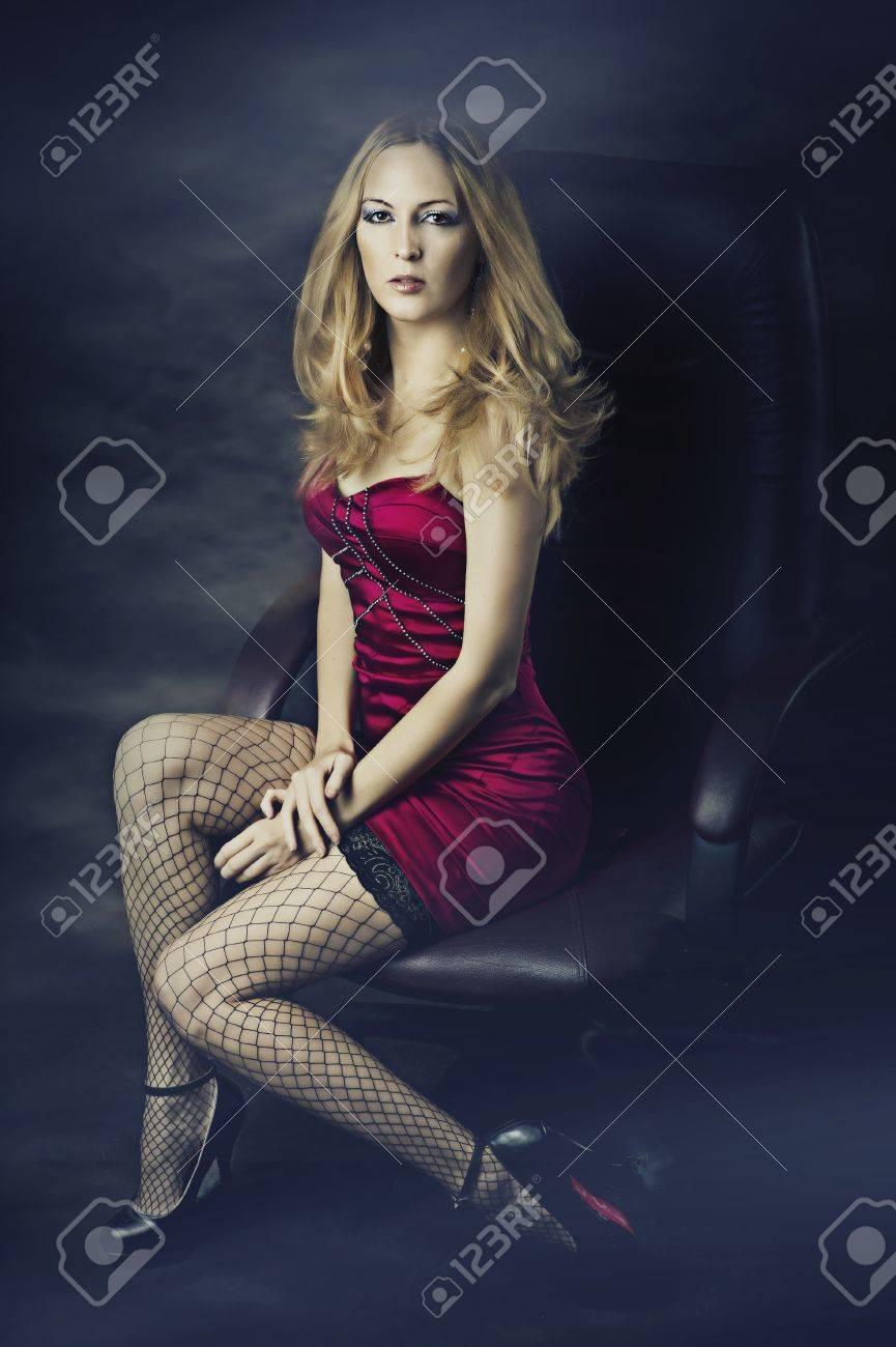 schöne blonde frau in sexy roten kleid und netzstrümpfe auf lange beine fit