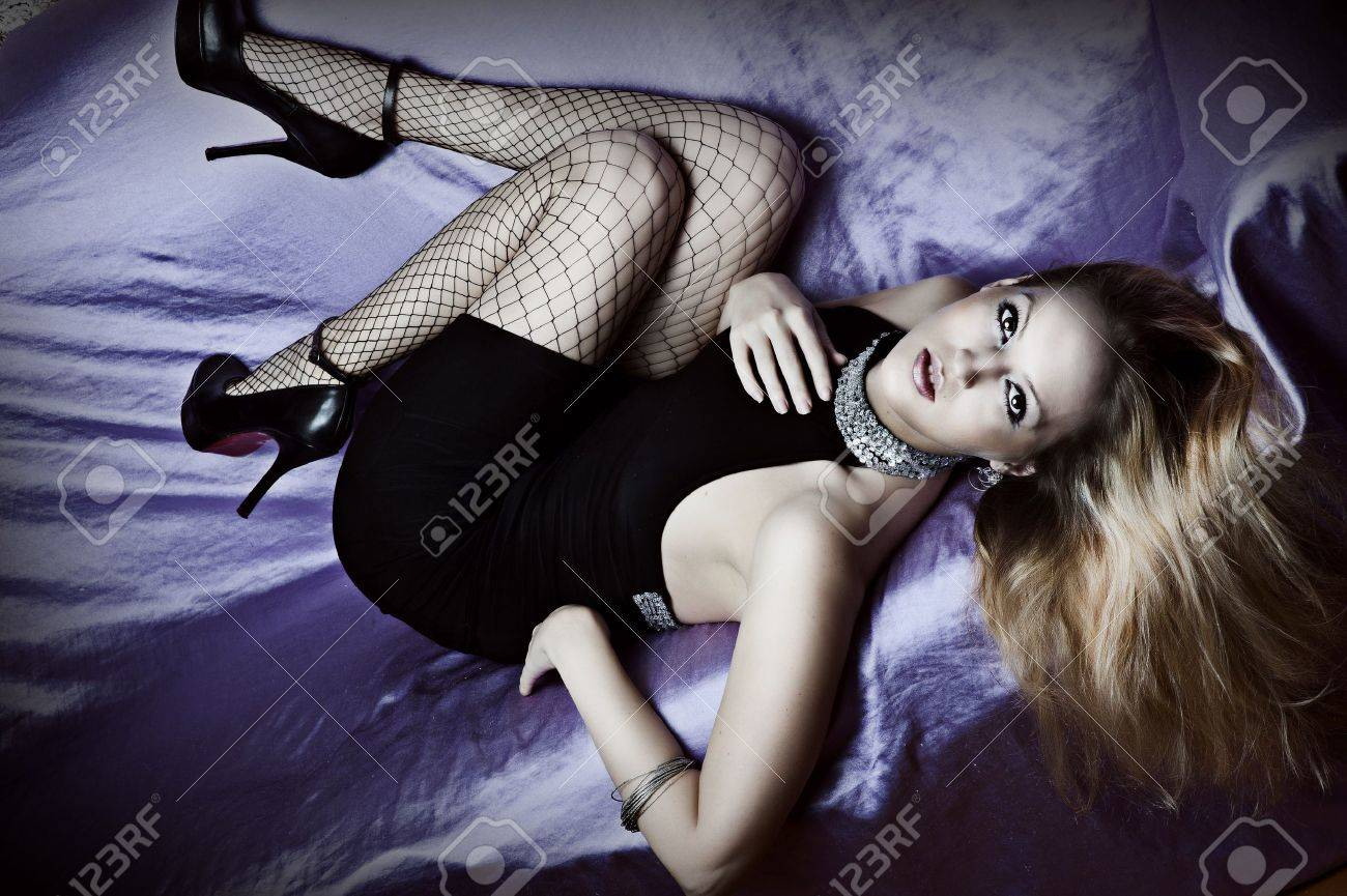 Sexy young woman on bed in black evening dress, high heel shoes and stockings Stock Photo - 12719252