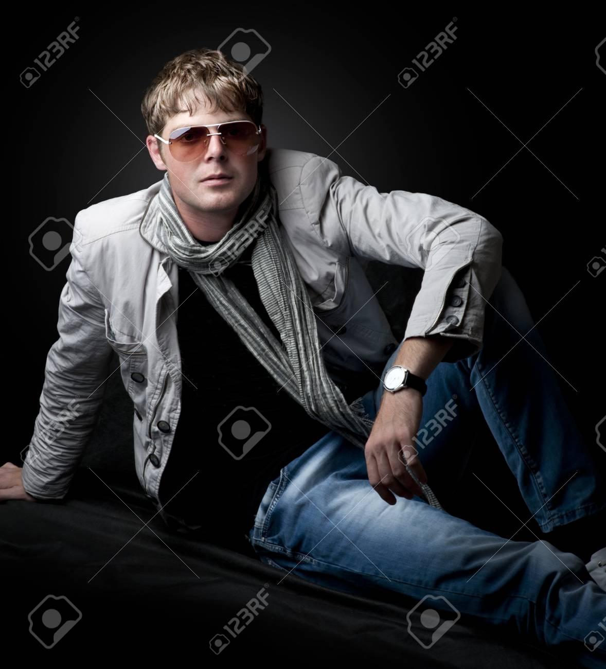 Young fashion man sitting on black background Stock Photo - 13889015