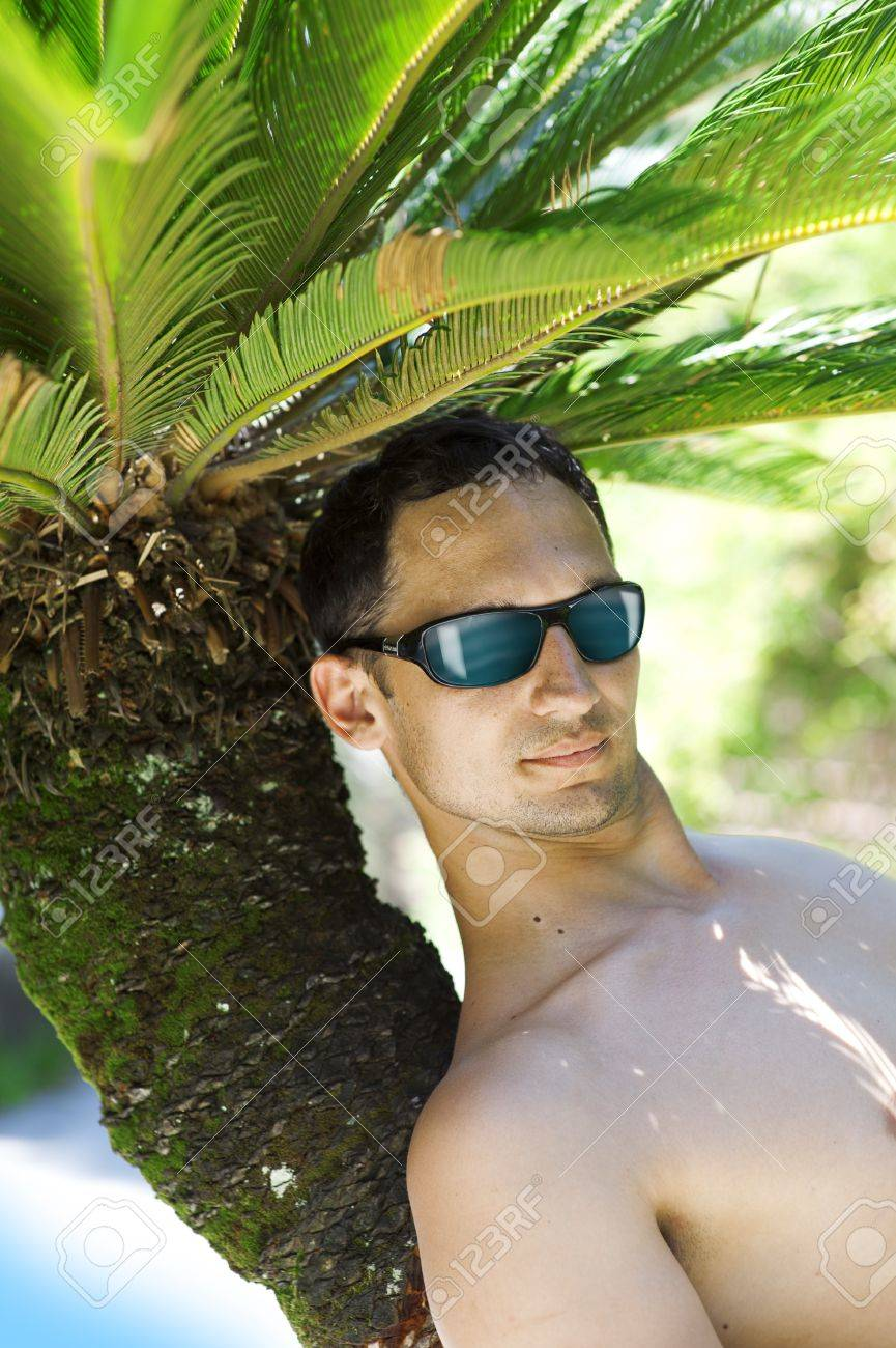 Fashion man lying upon palm tree on the beach Stock Photo - 14273265