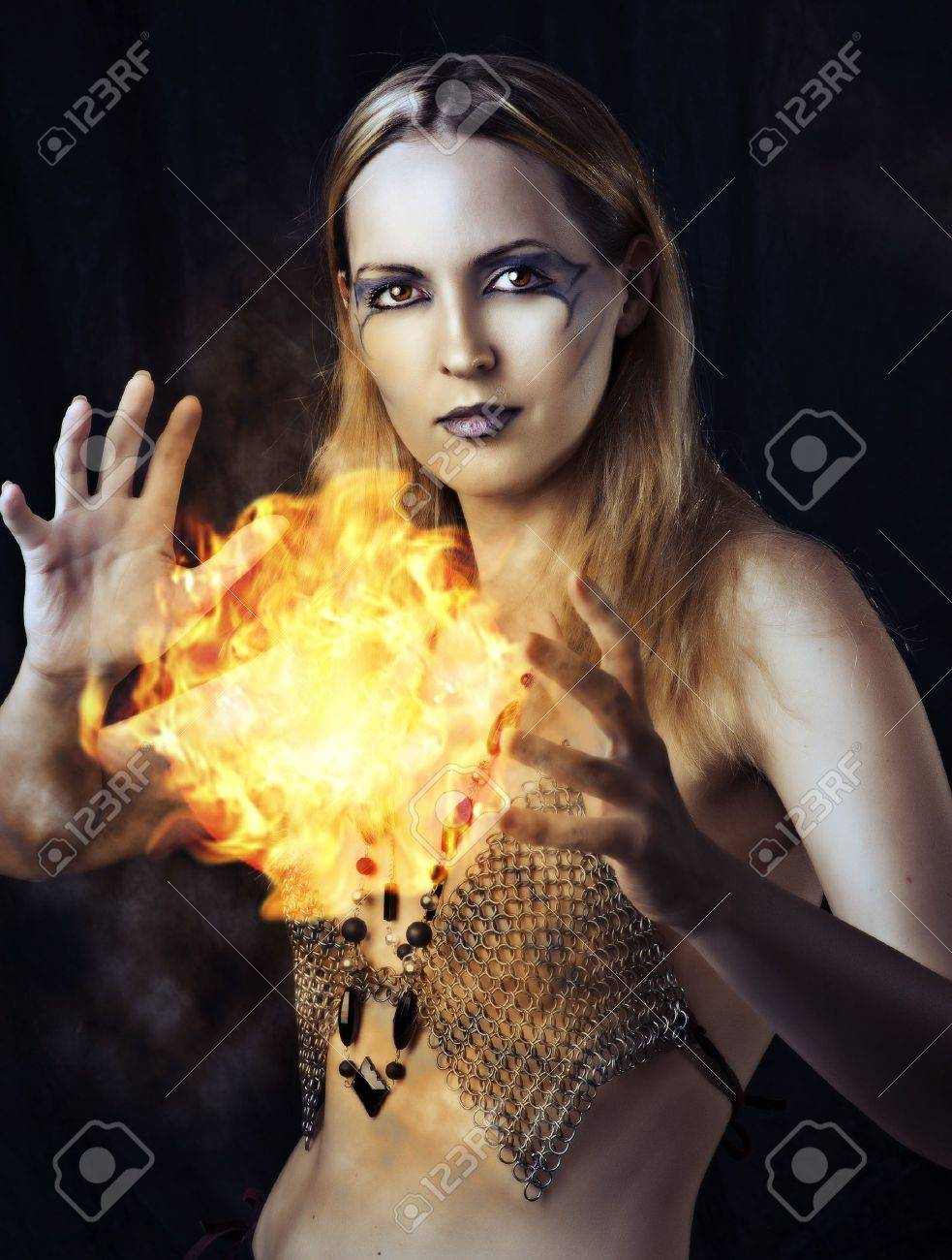 Portrait of dangerous woman witch with fire ball and dark make up Stock Photo - 14484868