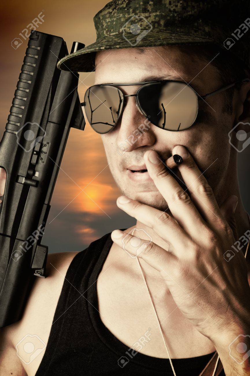 sexy military man wearing fashionable sunglasses and cap with automatic smoking a cigar Stock Photo - 14715598