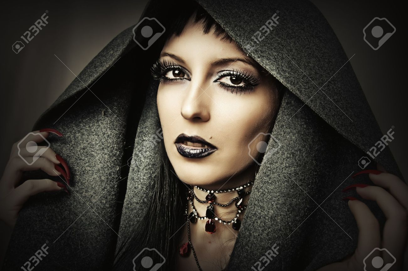 Young beautiful brunette woman in gray hood with fashion gothic make up and ancient necklace - 15127266