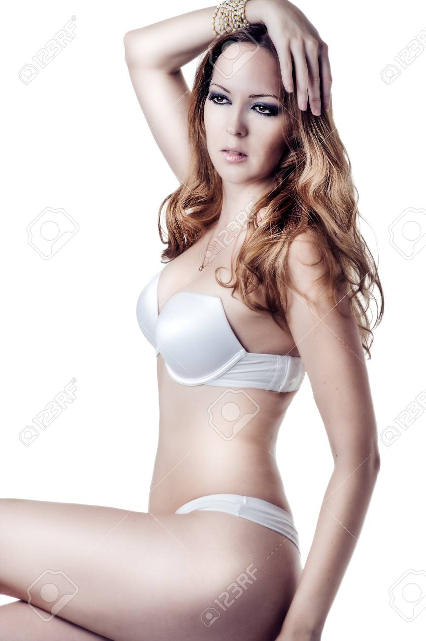 f0e6b09fd52 Stock Photo - young beautiful brunette woman wearing sexy lingerie sitting  at studio on white background