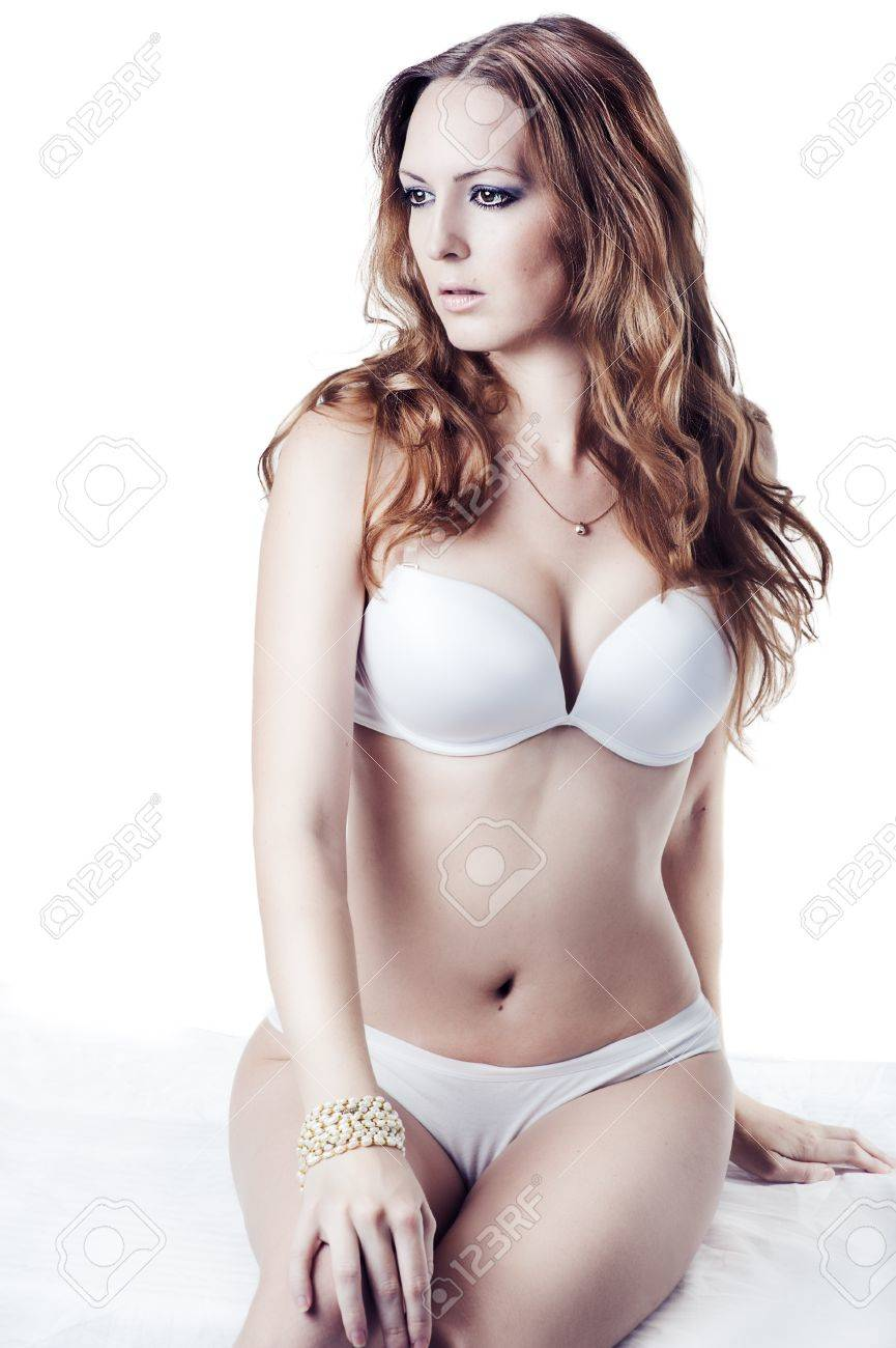 young beautiful brunette woman wearing sexy lingerie sitting at studio on white background Stock Photo - 16890321
