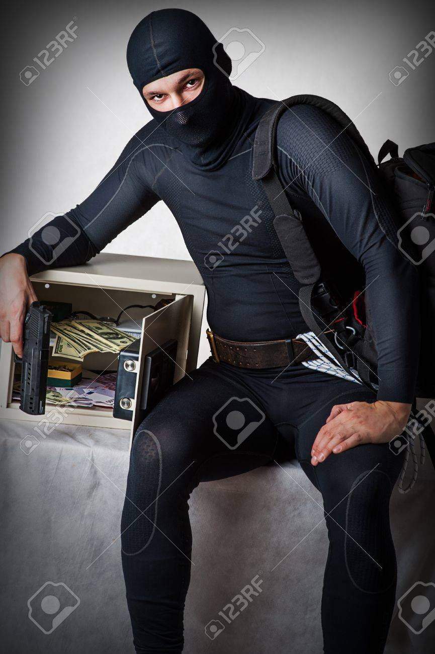 Professional burglar in black ski mask opened a small safe, holding hand gun Stock Photo - 16992972
