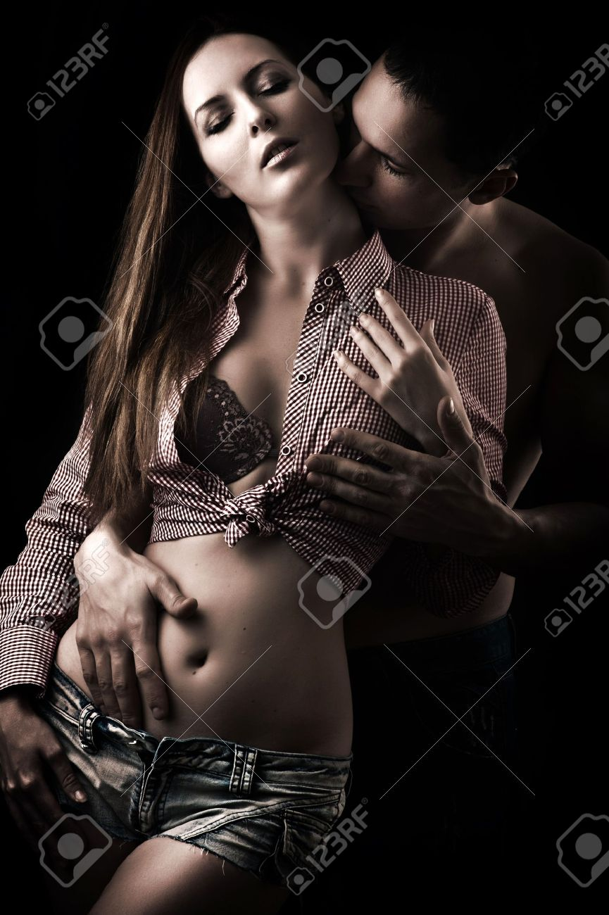 Emotive portrait of a young beautiful sexy couple on black background Stock Photo - 17847835