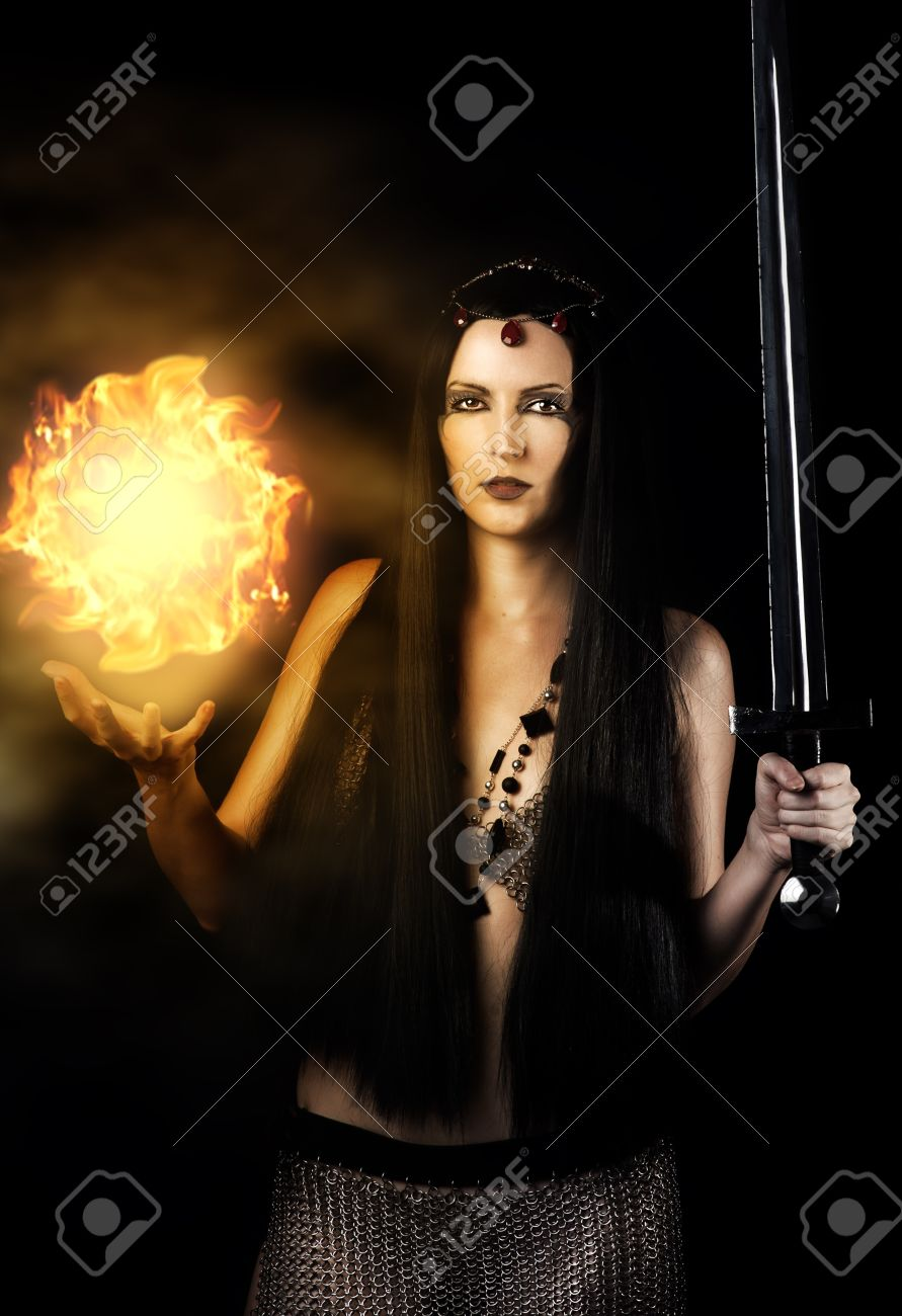 Young Sexy Woman Warrior With Long Black Hair Holding Sword And Magic Fire Ball In Hands
