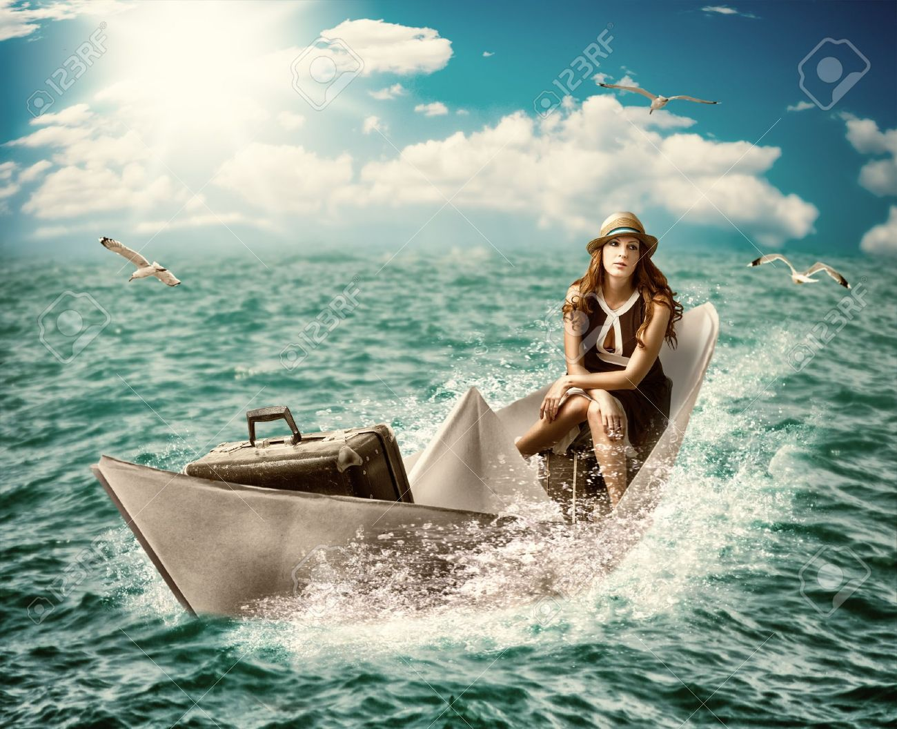 dreaming about sea cruise around the world.Woman with luggage floats on the paper boat on the ocean Stock Photo - 20258588