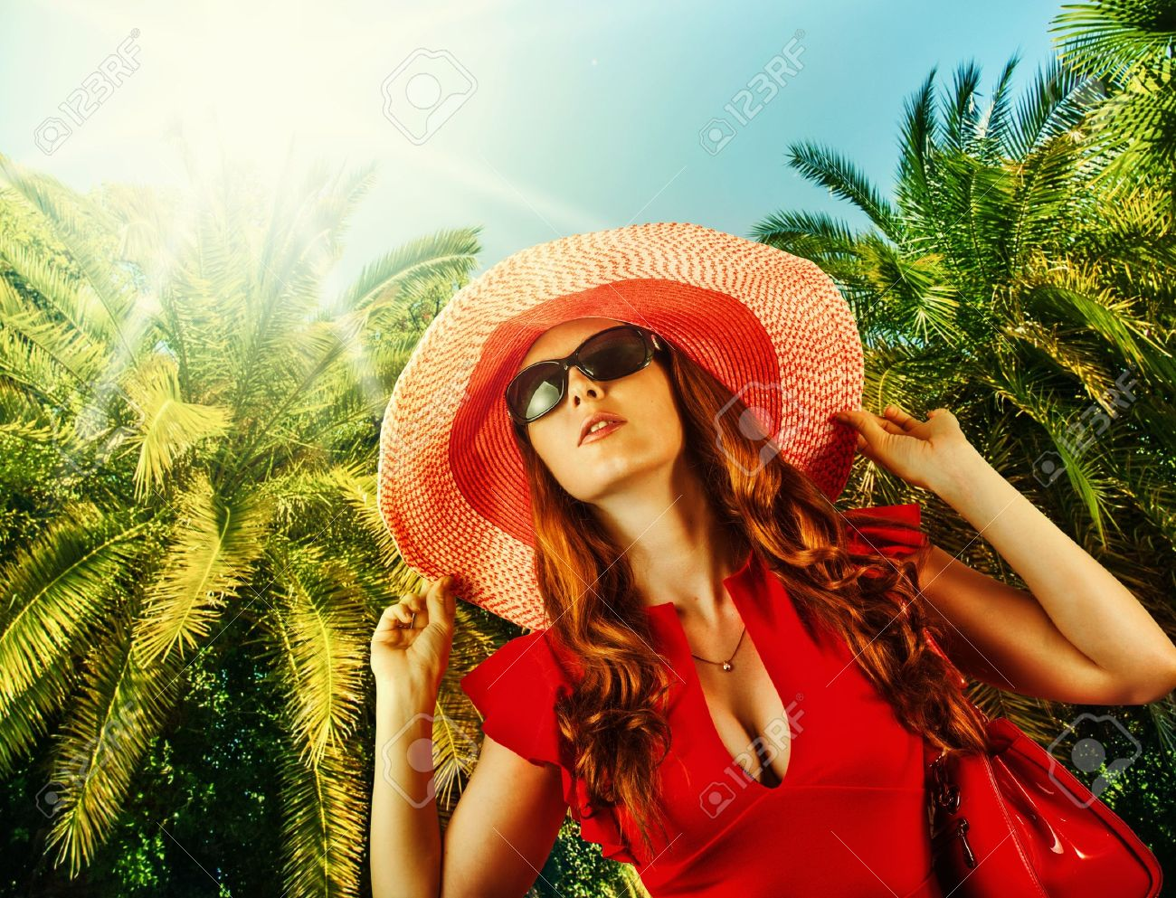 Young beautiful woman in red fashion dress, big hat and sun glasses on tropical resort Stock Photo - 20493577