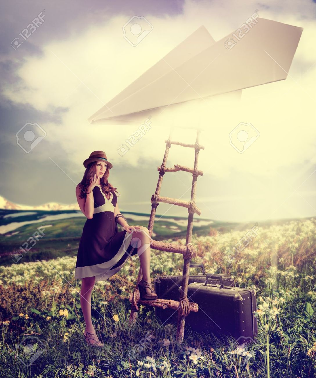 Concept - dreaming about travel.Beautiful woman with suitcases standing near the ladder to the paper plane in the clouds Stock Photo - 20438630