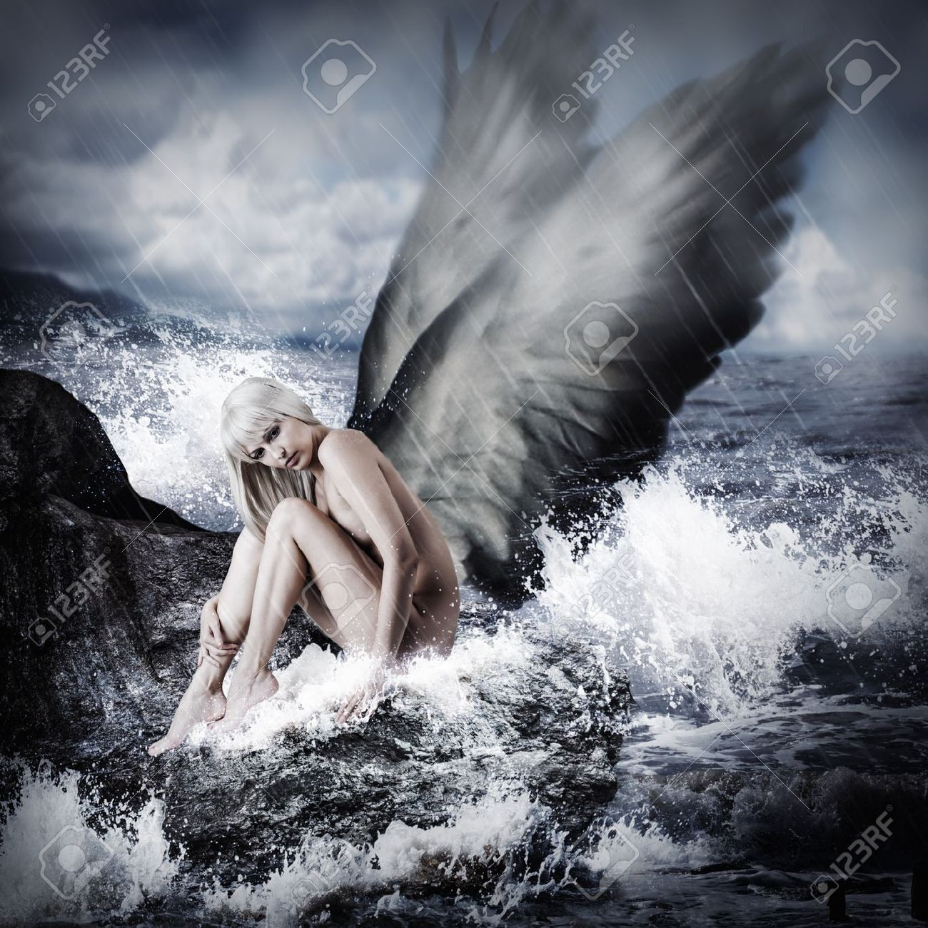 Sexy beautiful blond woman with angel wings sitting on a rock in the sea in storm Stock Photo - 21112347