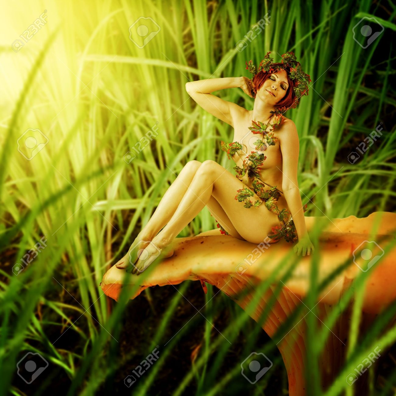 Young woman - Forest nymph sitting on chanterelle mushroom. Stock Photo - 21203136