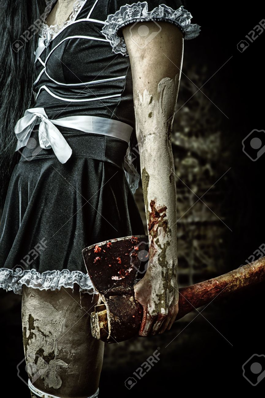 Horror. Dirty woman's hand holding a bloody ax outdoor in night forest Stock Photo - 21307837