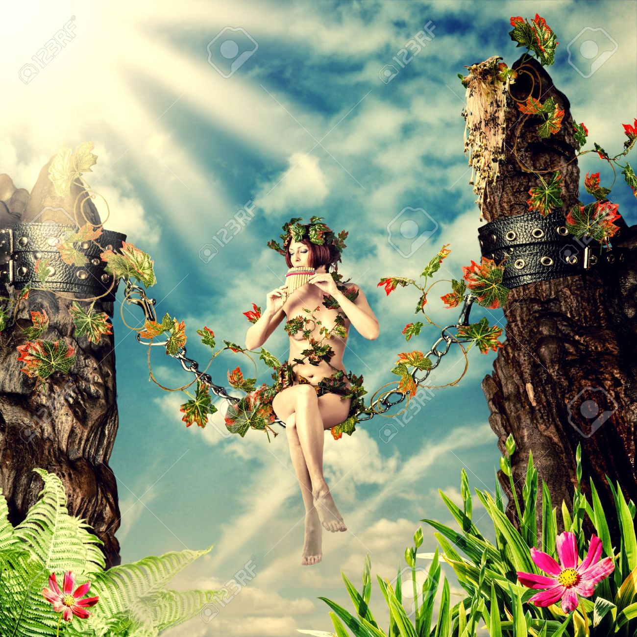 Young beautiful fairy woman playing the flute while sitting on a swing in the chain between the rocks and leaves Stock Photo - 21294316
