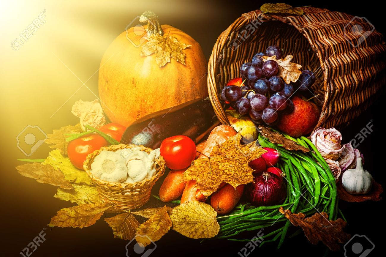 Beautiful autumn harvest of vegetables and leaves on black background with sun light Stock Photo - 21341935