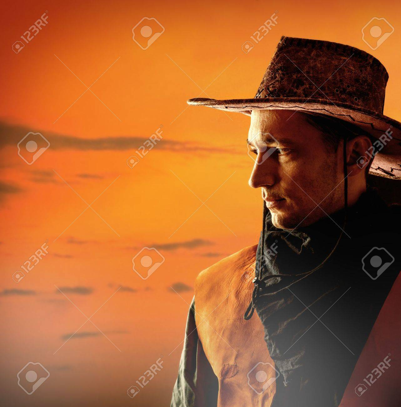 American cowboy in brown hat on a sunset background outdoor Stock Photo - 21622510