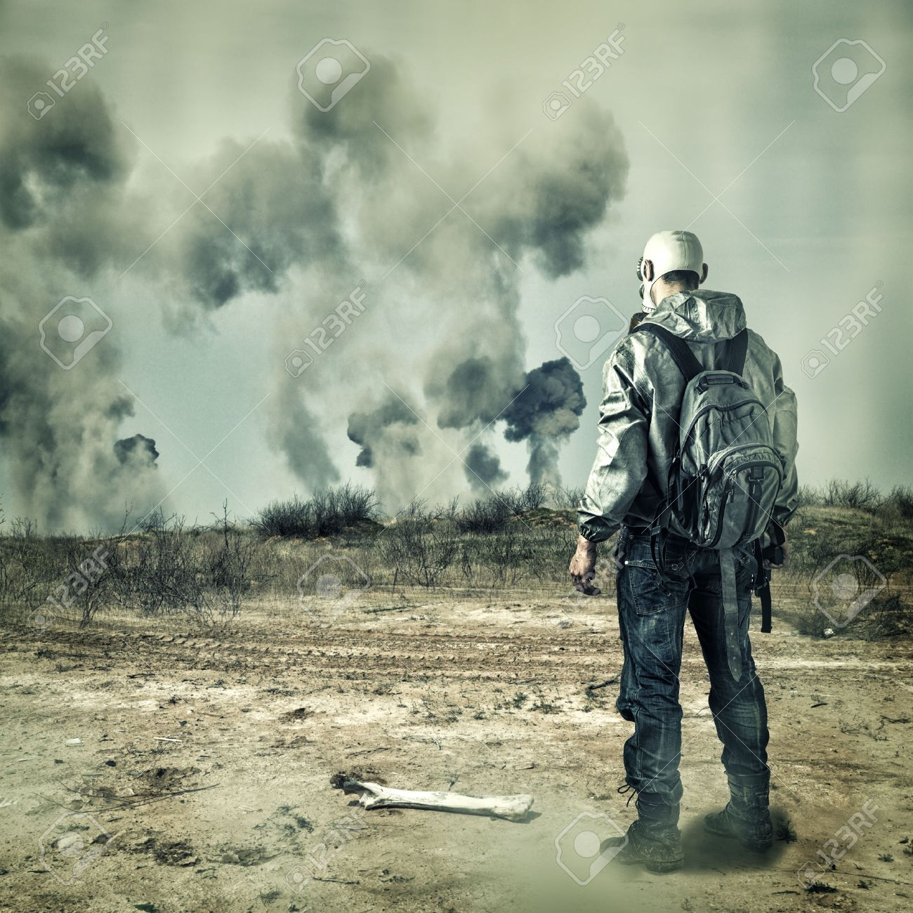 Post apocalypse. Man in gas mask with handgun and  back pack in apocalyptic world looking on explosions on horizon Stock Photo - 22188664