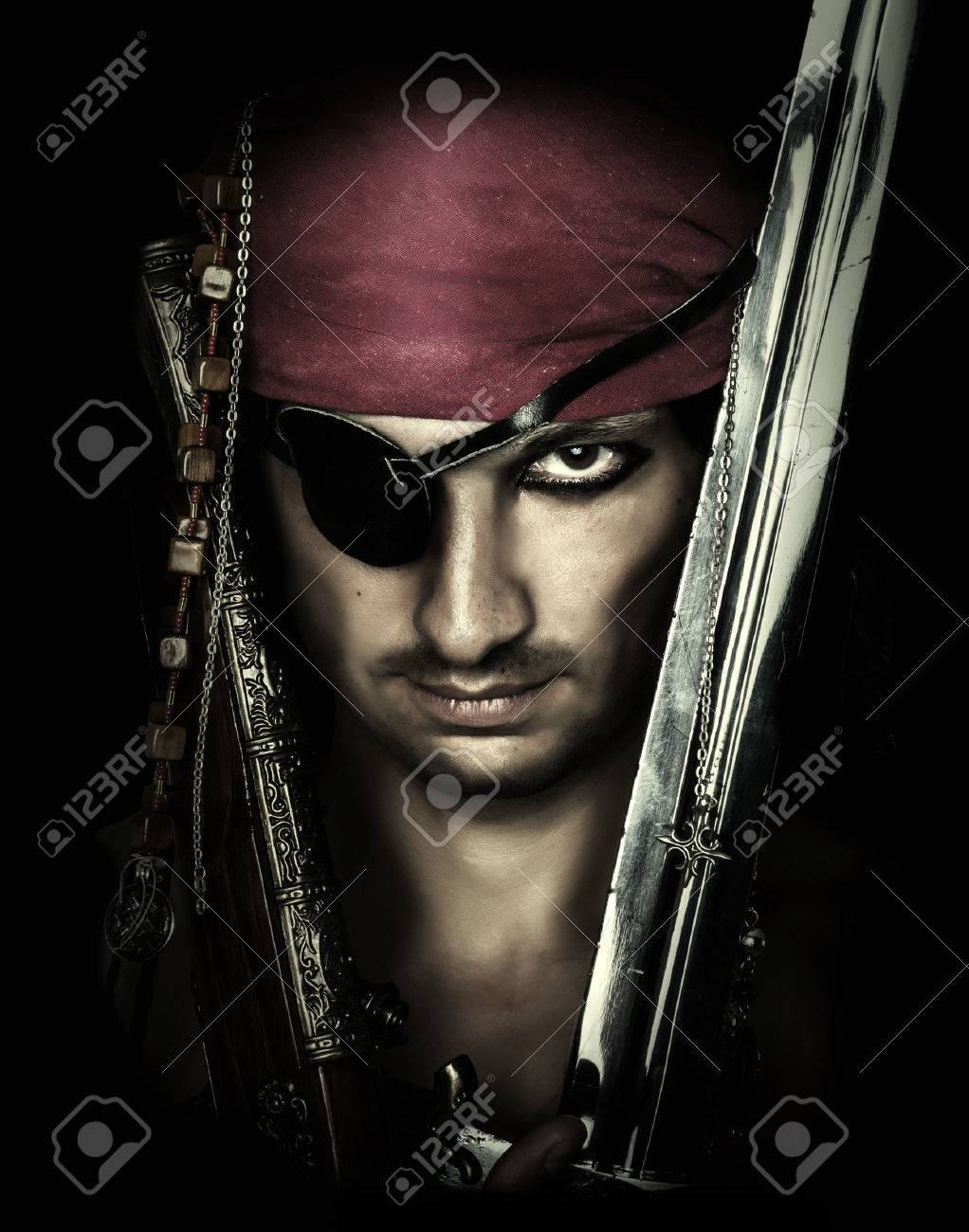 Portrait of handsome male pirate holding sword on black Stock Photo - 25465334