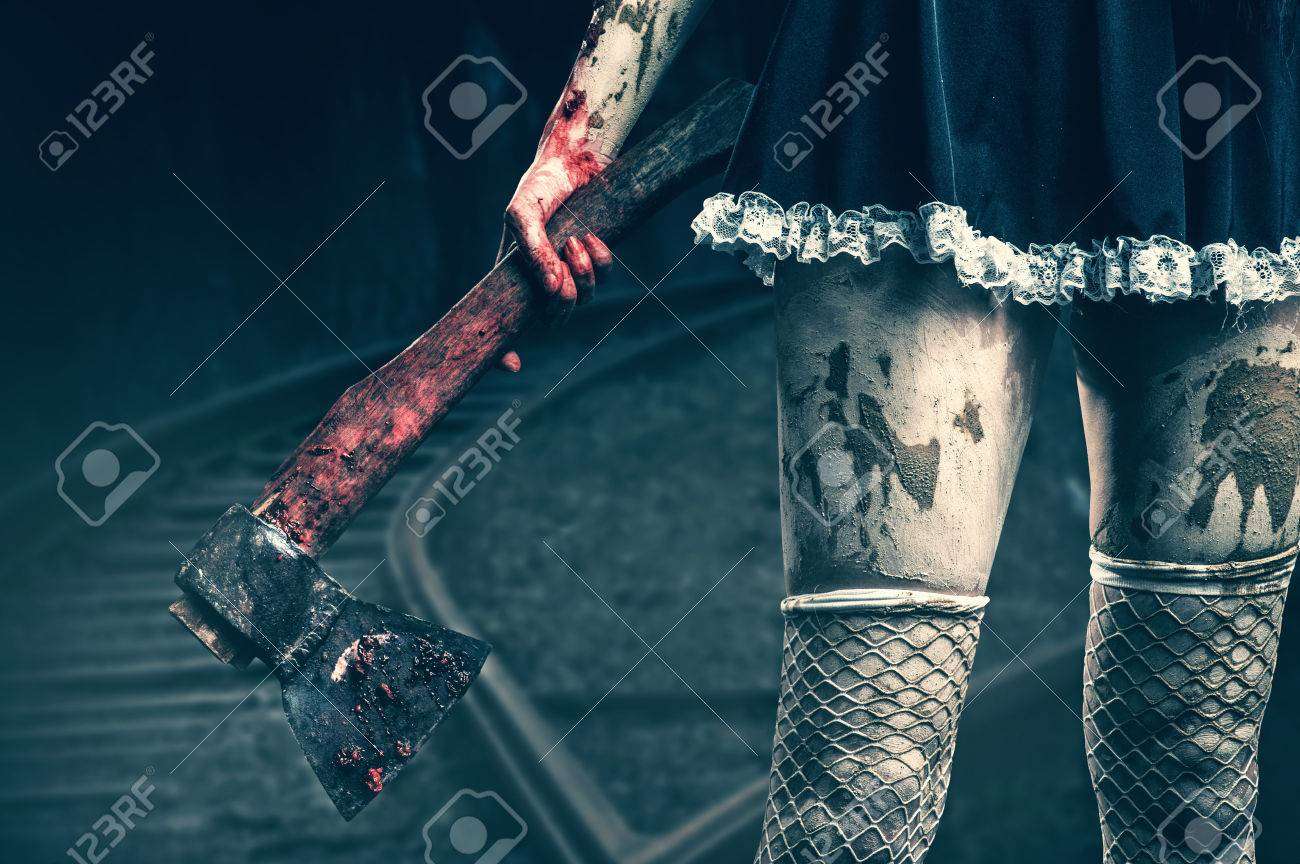 Horror. Dirty woman's hand holding a bloody axe outdoor in night forest Stock Photo - 32722977