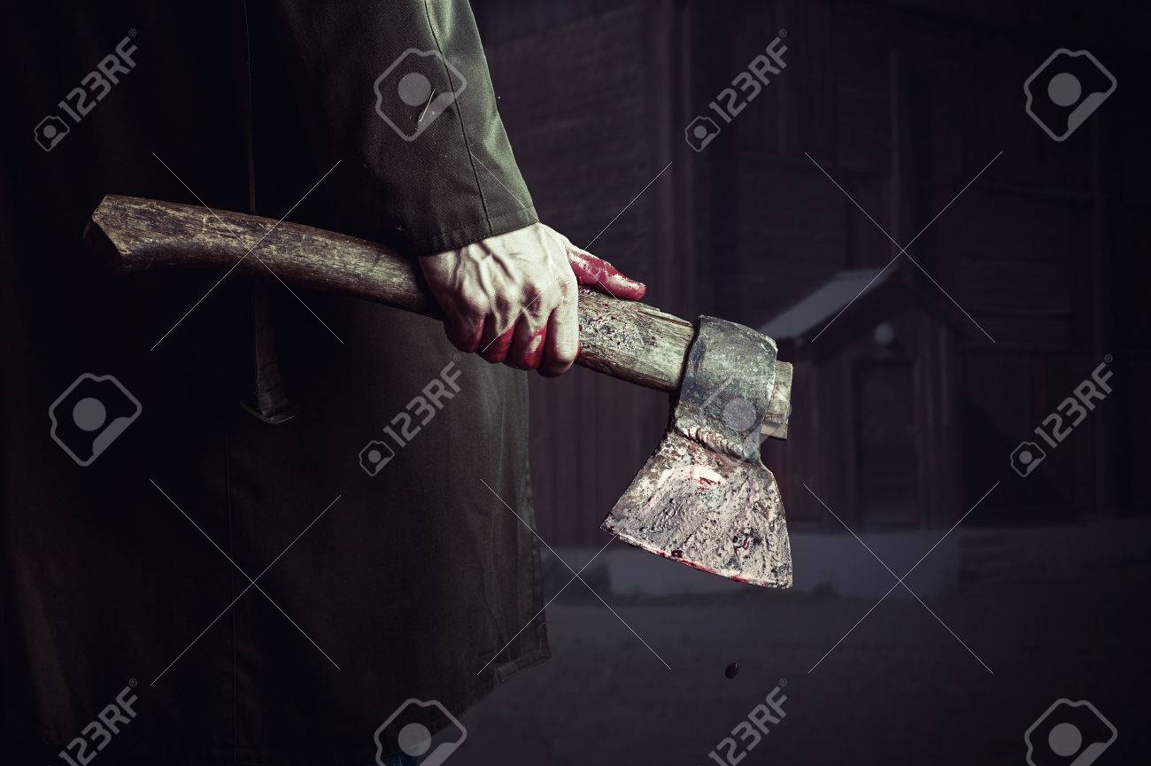 Axe with blood in male hand.  murderer or butcher, halloween theme Stock Photo - 32723013
