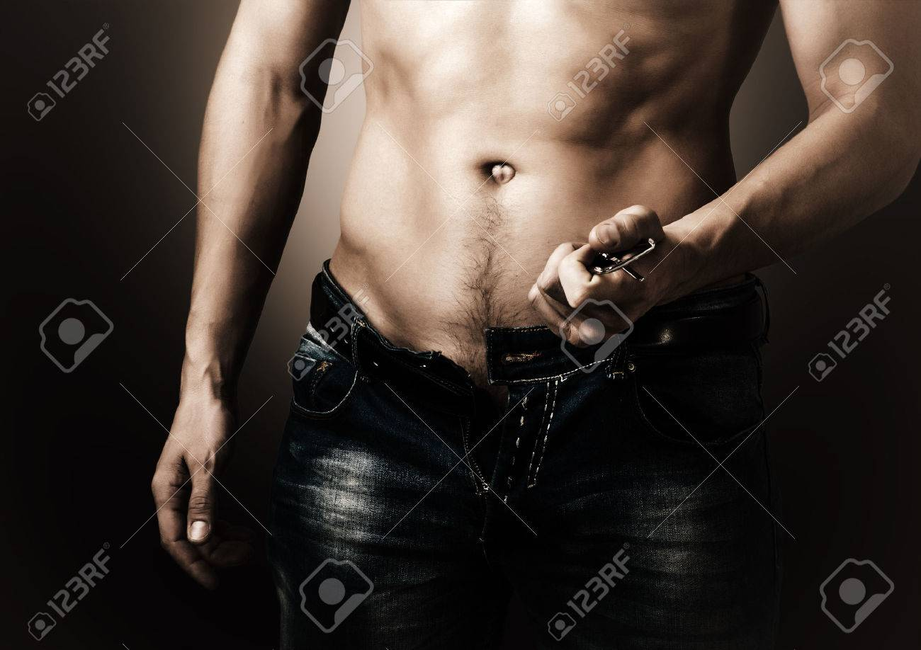 Man showing his muscular body. Stripper unzips jeans and belt Stock Photo - 33931227