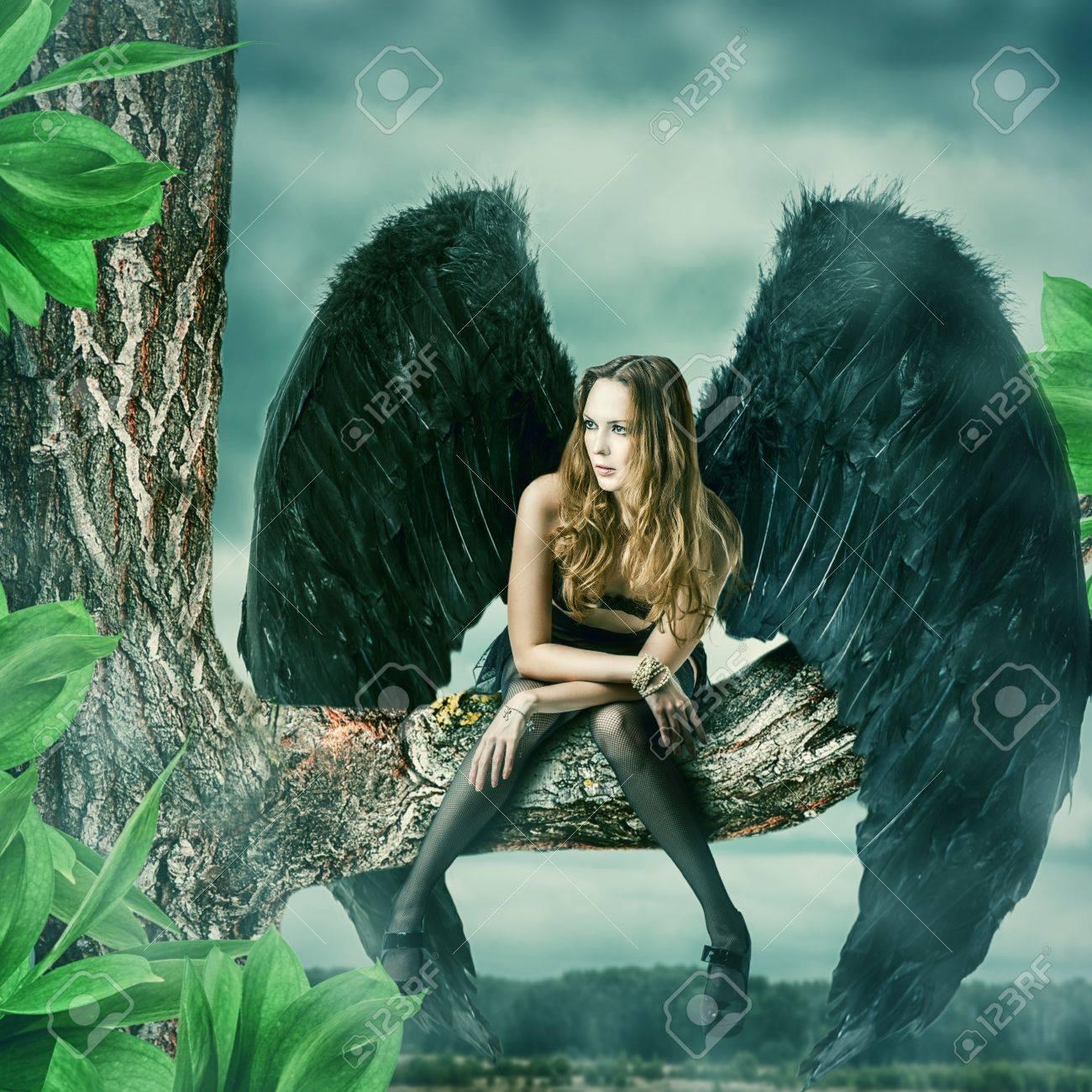 Beautiful female black angel sitting on a tree Stock Photo - 40818097
