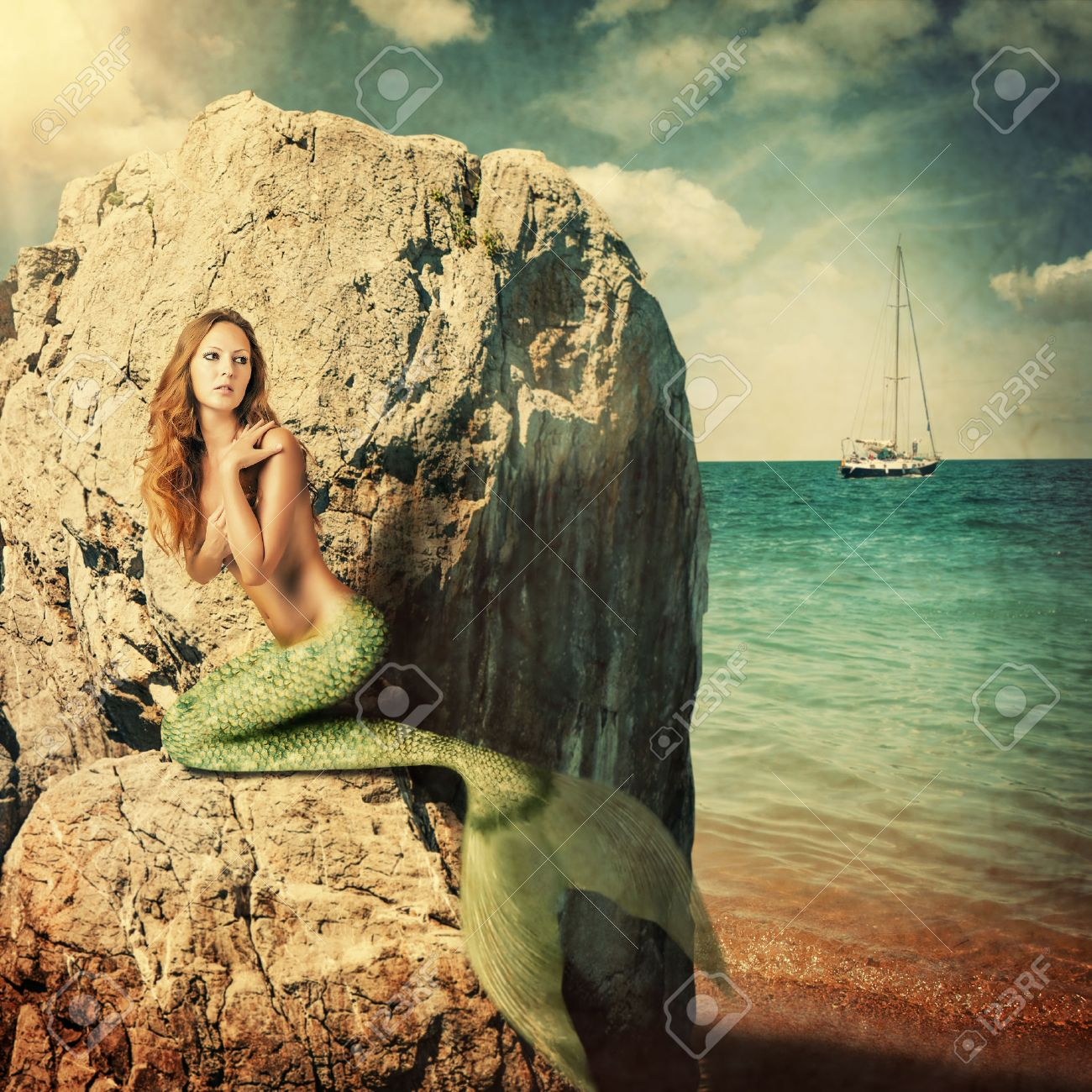 Sexy beautiful woman mermaid with long tail sitting on a rock about sea. Hiding from sailboat Stock Photo - 40818224