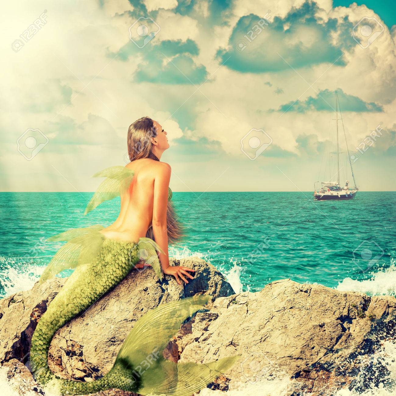 Beautiful Mermaid with fish tail sitting on rocks and looks at a ship on the horizon Stock Photo - 40818223